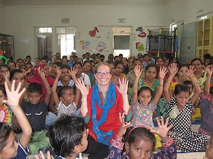 Photo of a Wolf Trap Teaching Artist surrounded by students in India