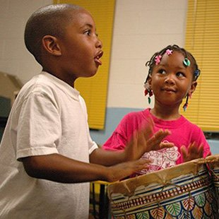 Photo of two young children playing a drum
