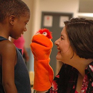 Photo of a student and teacher interacting with a puppet